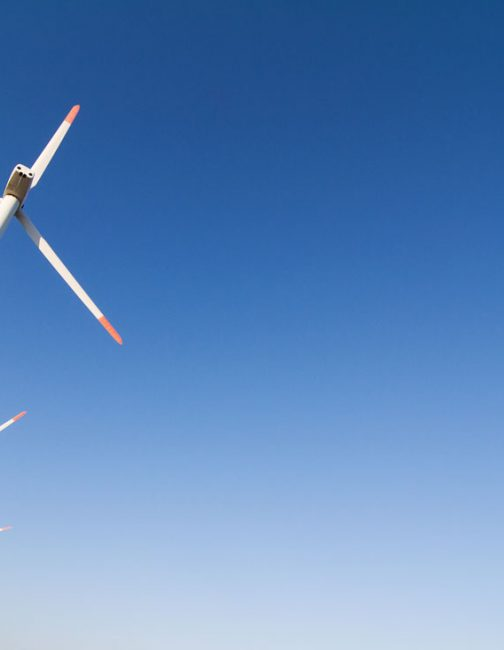 angled-view-of-wind-turbines-against-a-blue-sky-EDRYGP6